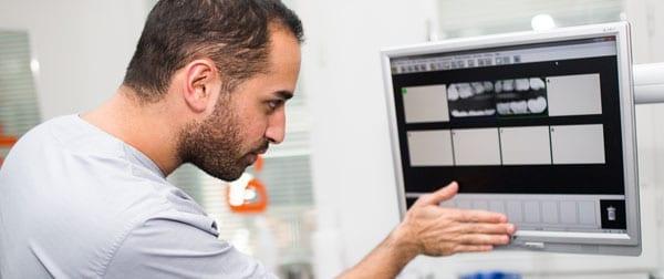 Manlig tandläkare tittar på röntgenbilder på skärm